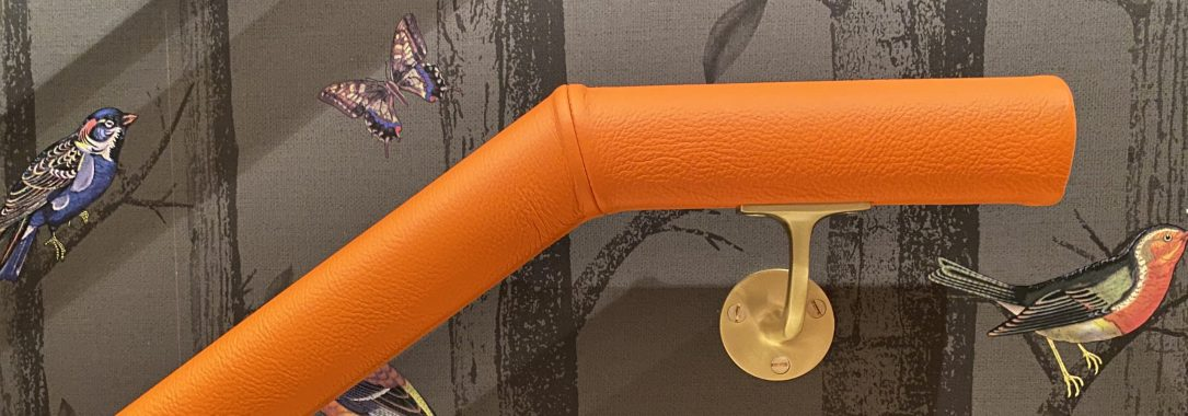 orange leather handrail with brass brackets